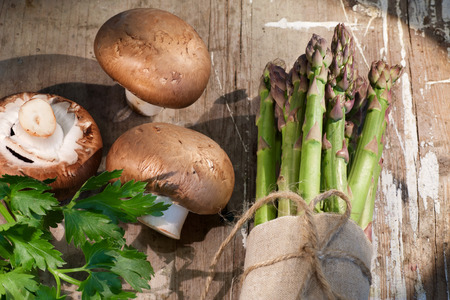 nahaufnahme: Asparagus and mushrooms on rustic wooden background Stock Photo
