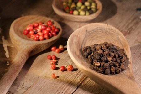rt: Top view of wooden spoon full of mixed colorful peppercorns Stock Photo
