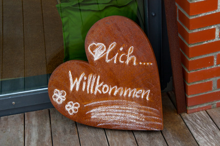 cordiality: A sign in heart shape with the inscription welcome Stock Photo