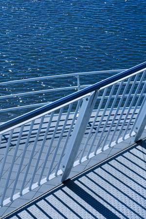 visually: Railings made of steel tubes in visually pleasing arrangement, with summer sun glinting on them Stock Photo