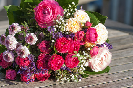 floristics: Romantic bouquet with pink roses on wooden table