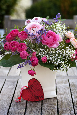 Romantic bouquet with heart and pink roses on wooden table Archivio Fotografico