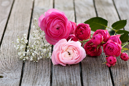 Romantic bouquet with pink roses on wooden table