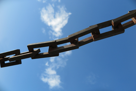 chain links: Heavy chain links in front of a blue sky