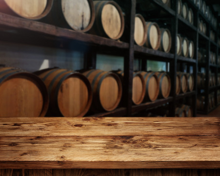 casks: rustic wooden table in front of wine barrels Stock Photo