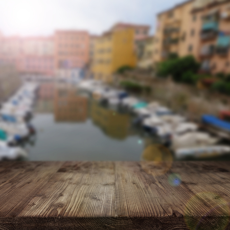 marina life: Wooden table in front of a marina with houses