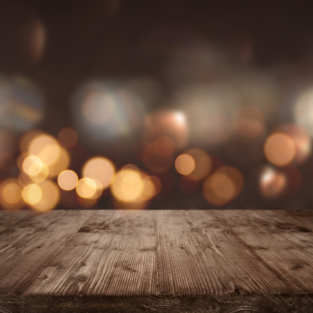 Dark abstract background with lights and bokeh in front of a wooden table Stock Photo