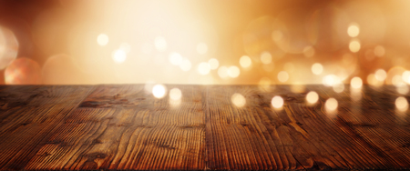 Christmas background with a string of lights in front of a wooden table