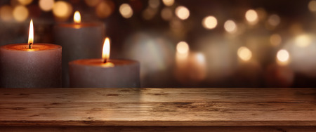 Christmas background with candle lights in front of a wooden table Imagens