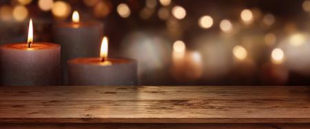 Kerst achtergrond met kaarsen in de voorkant van een houten tafel