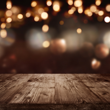 Dark abstract background with christmas lights in front of a  table Standard-Bild