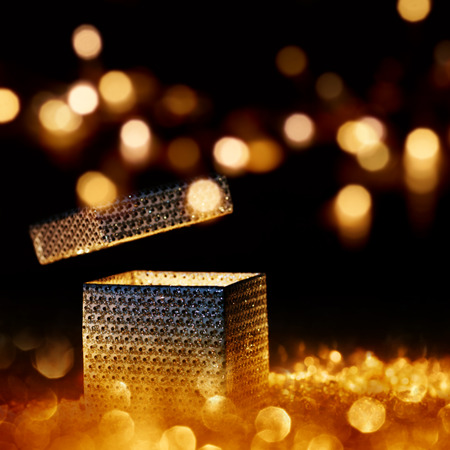 surprise box: Illuminated present for special moments in front of a dark Background