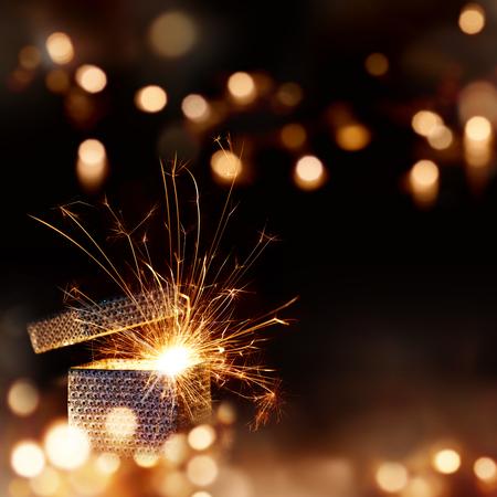 Cadeau surprise Radiant pour Noël devant un fond sombre avec des lumières et bokeh Banque d'images - 63841697
