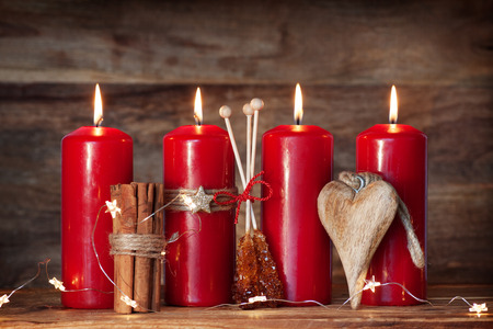 advent candles: Advent candles with cinnamon and candy in front of a wooden Background Stock Photo