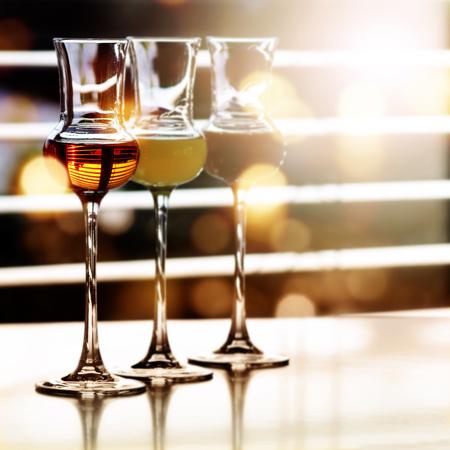 bebidas alcohÓlicas: Diversas bebidas alcohólicas en frente de una ventana con reflejos de sol Foto de archivo