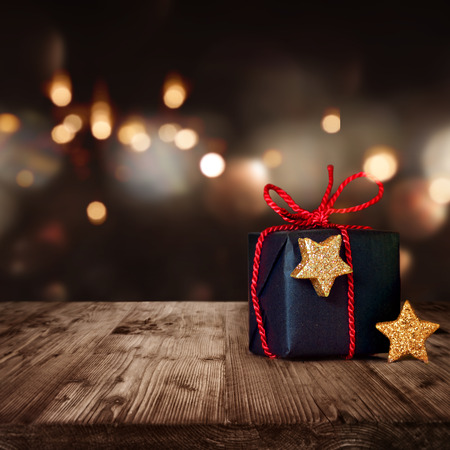 Christmas package with red bow in front of festive background Standard-Bild
