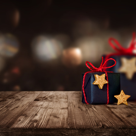 expired: Christmas parcels with red loop and golden stars on a wooden Table Stock Photo