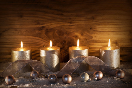 Still life with silver candles for the 4. advent in front of a wooden wall Standard-Bild