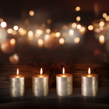 Silver candles in front of a festively lit background with bokeh