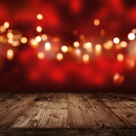 Luminous red christmas background with golden lights in front of an empty wooden table Standard-Bild