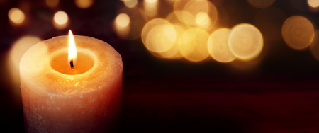 Candles with golden lights against a dark background with bokeh