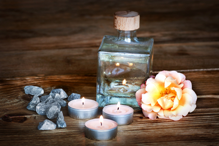 perfumed candle: Spa still life with aromatic oil on a dark wooden table for a concept Stock Photo
