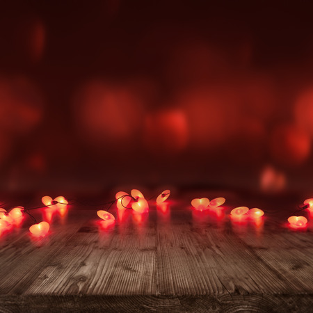 decorate: Valentines day background with burning hearts in front of a empty wooden table for a concept Stock Photo