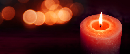 Burning candle for silence moments on a dark background with red light