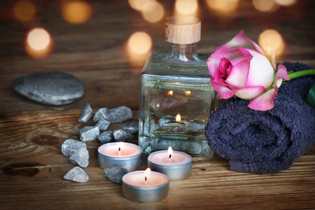 perfumed candle: Spa still life on a wooden table with a violet towel and bokeh