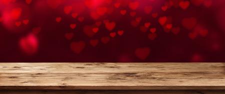 Panorama with flying red heart in front of an empty wooden table for valentines Day