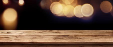 panorama oscuro con la luz de oro de los días festivos en frente de una mesa de madera vacía para un concepto