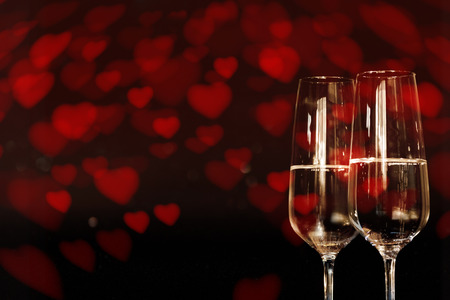 Dark Background with red heart and two champagne glasse for love greetings