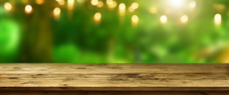 eastertime: Spring background in a park with yellow bokeh in front of a wooden table