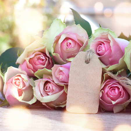 Bouquet of rose with a card for mothers day on a wooden table and bokeh Stock Photo