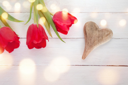 White wooden background with tulip and a heart for mothers day