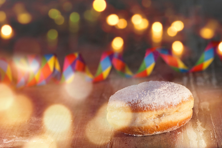 Delicious donuts on wood with colorful air streamer and bokeh for carnival and party Standard-Bild