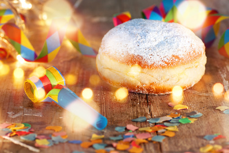 caterers: Delicious donuts on a wooden table with confetti and bokeh for carnival and party