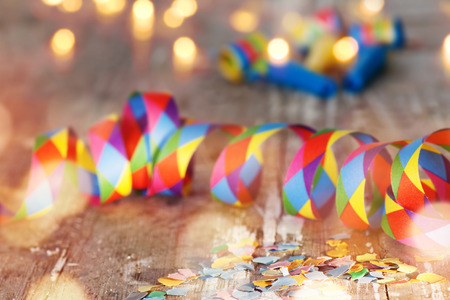 fasnacht: Colorful confetti and air streamer on rustic wooden table with bokeh