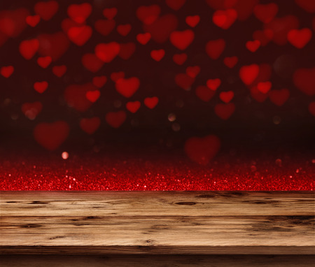 Red love heart in a dark background in front of a empty wooden table for a valentines day concept Stock Photo