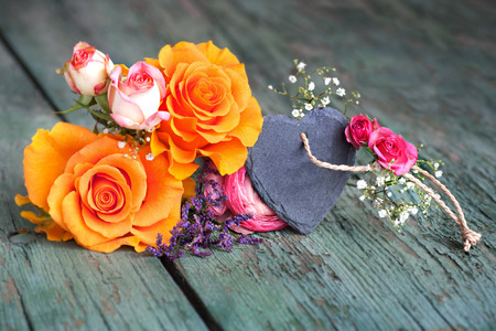 bunch of hearts: Flower decoration with a heart from slate on an old shabby wooden table for mothers day or valentines day Stock Photo