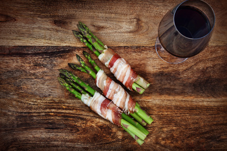 secondhand: Green asparagus with bacon and a glass of red wine on a dark rustic wooden table Stock Photo