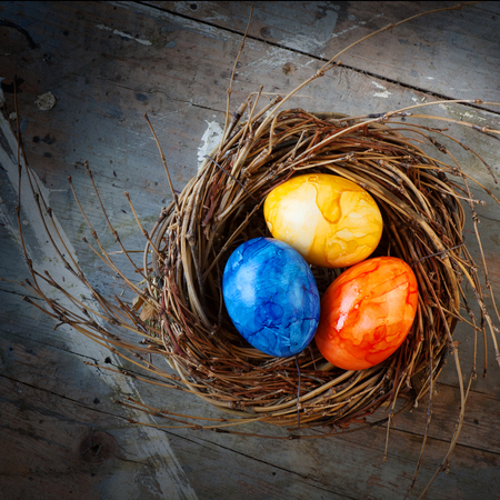 eastertime: Colorful easter eggs in a nest from straw on a old shabby wooden table