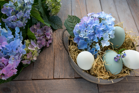 eastertime: Easter decoration with flowers on a dark shabby wooden table Stock Photo