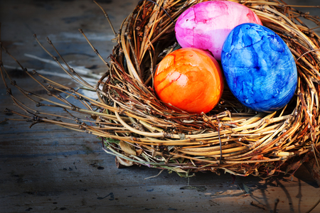 eastertime: Easter eggs in radiant colors in a nest on an old shabby wooden table