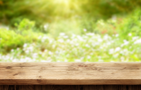 Wooden desk on bright sunny bokeh background for spring or summer time