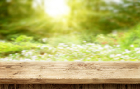 Wooden desk on bright sunny bokeh background for spring or summer