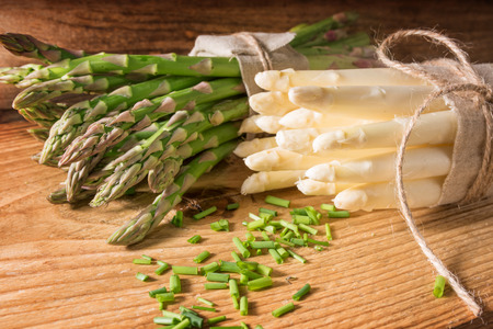lose up: Fresh green and white asparagus with parsley on a wooden table Stock Photo