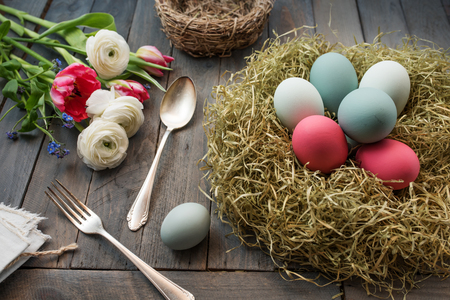 eastertime: Still life with colorful easter eggs in a nest and flowers on a old shabby wooden table Stock Photo