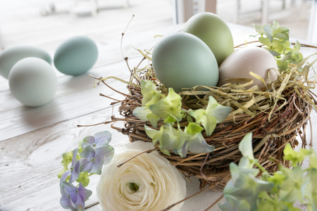 eastertime: Still life with pastel colored easter eggs in a nest of straw and flowers on a white wooden table