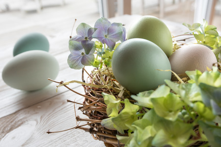 eastertime: Easter decoration with pastel colored eggs in a nest of straw on a white wooden table